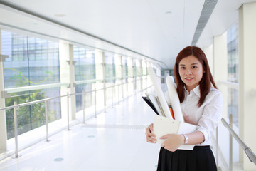 Businesswoman holding a box of items.