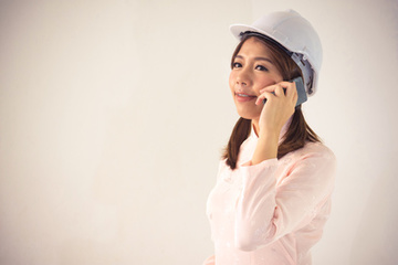 Lady in a hardhat on the telephone.