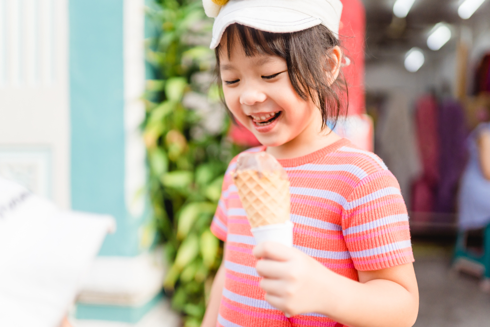 Happy Little asian girl walking and enjoy eating chocolate soft cream cone or ice cream cone at street in summer season